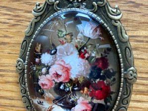 Kukat mustassa maljakossa, rintaneula
